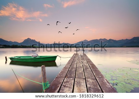 Photo of  wooden jetty at the lake, boat on the lake