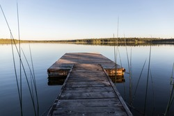 wooden jetty in a calm lake that looks like a mirror, in the background trees are reflected, next to the jetty reeds grow