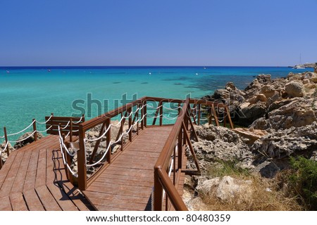 Wooden jetty leading to beautiful sea water of Konnos Bay on Cyprus island