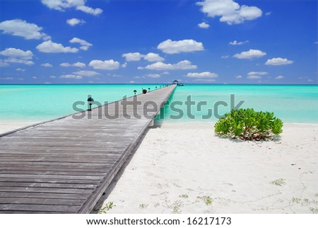 Wooden jetty on over the beautiful Maldivian beach with blue sky and clouds stock photo