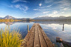 wooden Jetty on the lake named Hopfensee with the Alps and blue sky