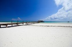 Wooden jetty on white sand tropical beach on Zanzibar island