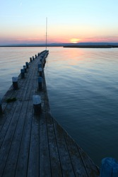 Wooden jetty or dock with piers in colorful sunset light, surrounded by calm water, in the background golden sun and land, selective focus into middle part of image