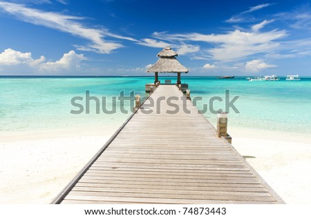 Wooden jetty over the beautiful Maldivian sea with blue sky stock photo