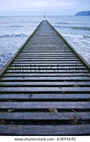 wooden jetty vanishing out into a winter seascape with a way marker at the vanishing point