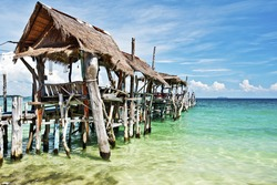 Wooden jetty with roofs in tropical beach of Ko Samet island, Thailand