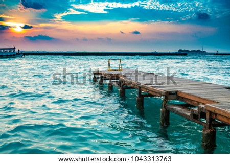 Wooden jetty with sunset background. #1043313763