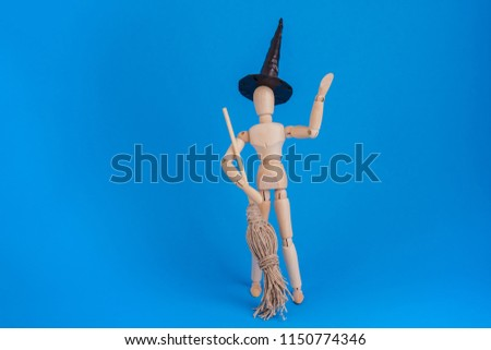 Wooden jointed dummy doll waving dressed as a Halloween witch black witch hat holding a broom on blue backdrop #1150774346