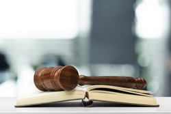 Wooden judge gavel on table, front close-up view
