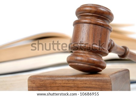 Wooden judge's gavel and books in the background, isolated on white