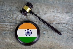 Wooden judgement or auction mallet with of India flag. Conceptual image.