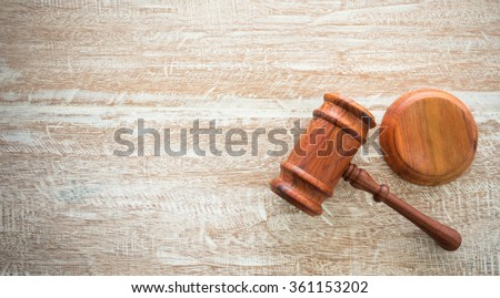 wooden judges gavel and soundboard resting on top of wooden desk. auctions concept.