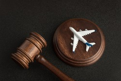 Wooden Judges gavel and toy plane. Aviation Law. To sue the airline