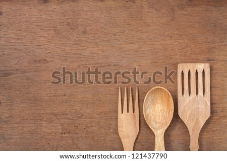 Wooden kitchen spoons, forks on oak wood table background