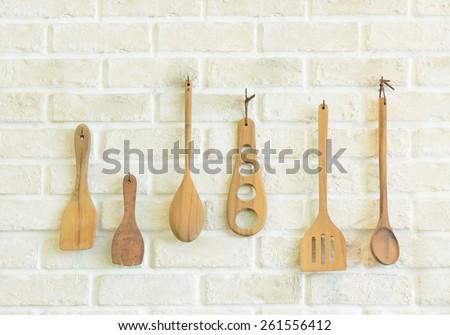 Wooden kitchen utensils on white brick wall