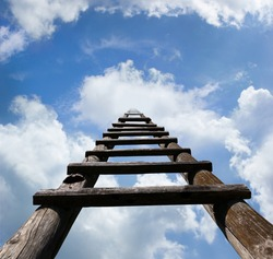 Wooden ladder leading high up in the heavenly looking blue sky and white clouds, success concept