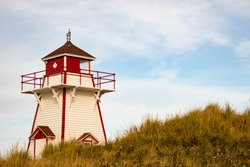 Wooden landmark lighthouse wiith Canadian maple leaf on red  along coast of Prince Edwards Island on the Ann of Green Gables Scenic Drive.