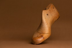 Wooden last for the manufacture of men's or women's footwear. Dark background.