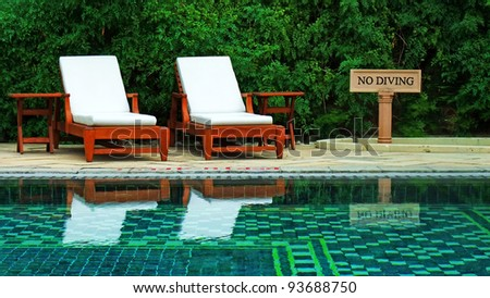 Wooden lawn chairs in a luxury hotel swimming pool, India