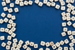 Wooden letter blocks over blue background, top view. Copy space.