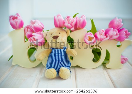 wooden letters baby background covered with spring flowers pink tulips and teddy bear on white floor