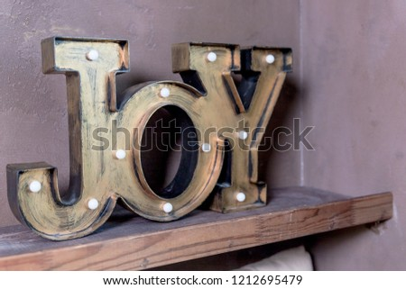 Wooden letters forming word Joy written on grey wall.Christmas postcard. The inscription: Joy to the world. Perfect design for greeting cards,Season of joy.Home decor joy with bulbs on brown #1212695479