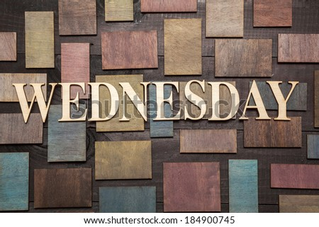 Wooden letters forming word WEDNESDAY written on wooden background
