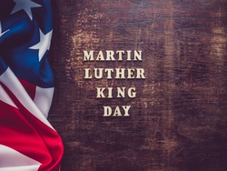 Wooden letters on a dark background. Martin Luther King Jr. Day. Top view, close-up. National holiday concept