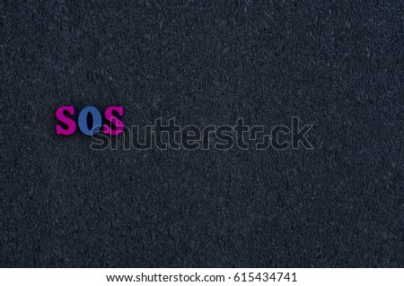 Wooden letters on the black surface, empty space on the right, the word sos #615434741