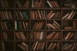 Wooden library bookshelves with aged paper books. Front view. Education concept. Retro background or wallpaper. Toned image.