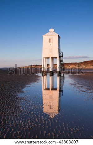 Wooden lighthouse built out of oak on the sandy beach at Burnham-on-Sea at sunset. Th structure is reflected in a tidal pool.
