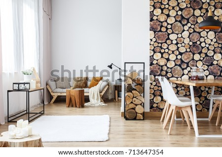 Wooden log texture wallpaper in cozy dining space of white open plan apartment with sofa, rug and tree stump accessories