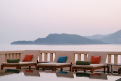Wooden loungers near the pool at the villa by the sea, at sunset.
