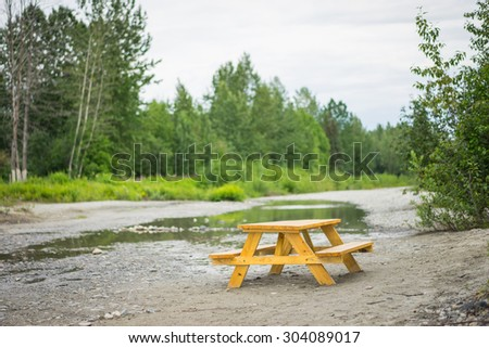 Wooden lunch table beside a calm stream in the woods and forest of Alaska.
