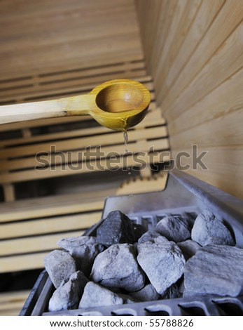 wooden luxury sauna indoor with hot stones and falling splashing water