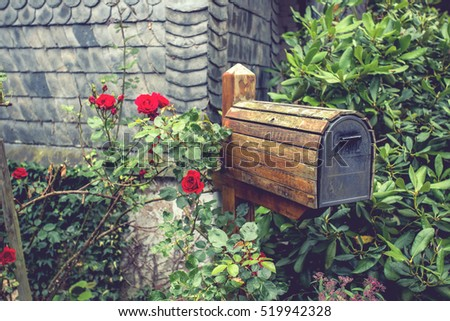 wooden mail box in flower garden ,vintage color tone.