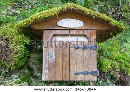 Wooden mail box with lichen on the top