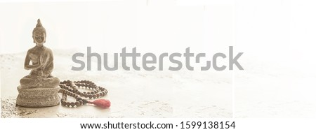 Wooden mala beads and Buddha statue on white concrete background with copy space. Essential accessory for mindfulness or meditation Stock photo ©