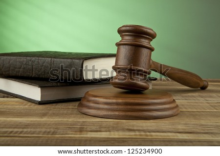 wooden mallet and books on a green background