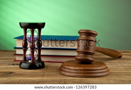 wooden mallet and books on a green background - stock photo