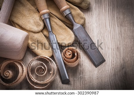 Wooden mallet curled up planning chips firmer chisels leather gloves on wood board construction concept. #302390987