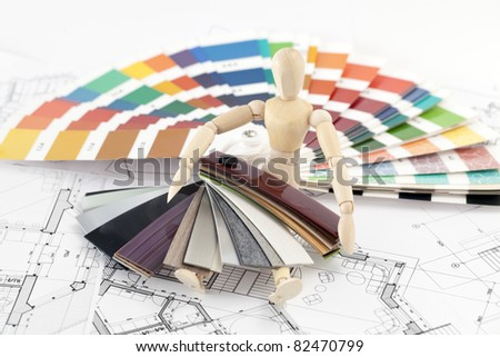 wooden man, a palette of colors designs for interior works, samples of plastics, PVC, for furnishing and architectural drawings houses