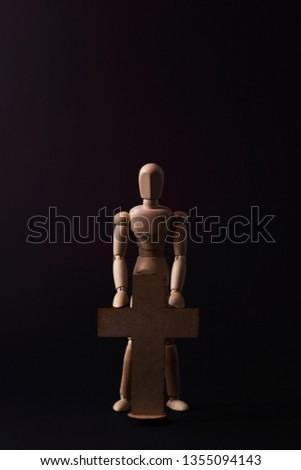 Wooden man. A wooden man holds a cross. Cross. Cross in hand. Wooden mannequin.  #1355094143