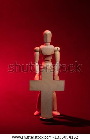 Wooden man. A wooden man holds a cross. Cross. Cross in hand. Wooden mannequin.   #1355094152