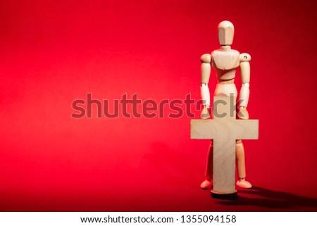 Wooden man. A wooden man holds a cross. Cross. Cross in hand. Wooden mannequin.  #1355094158