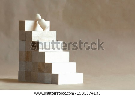 Wooden man falls from a professional ladder. Professional failure concept.