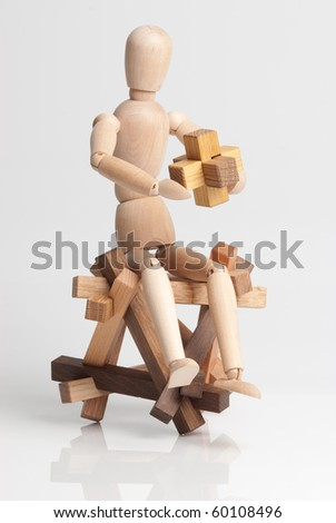 Wooden man figure solve the puzzle, and sits on an other puzzle.