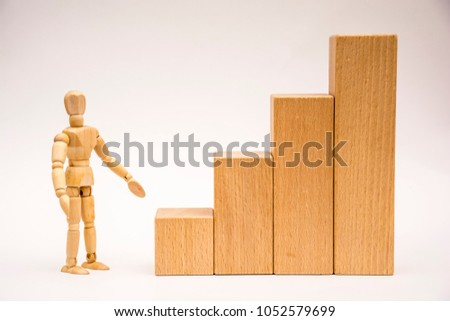 Wooden man stands in front of a high staircase and points to the first step, he looks at the viewer (front view) #1052579699