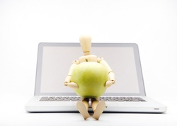 wooden man with computer take apple