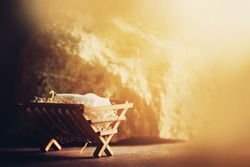 Wooden manger and star of Bethlehem in cave, nativity scene background. Christian Christmas concept. Birth of Jesus Christ. Jesus is reason for season. Salvation, Messiah, Emmanuel, God with us, hope.